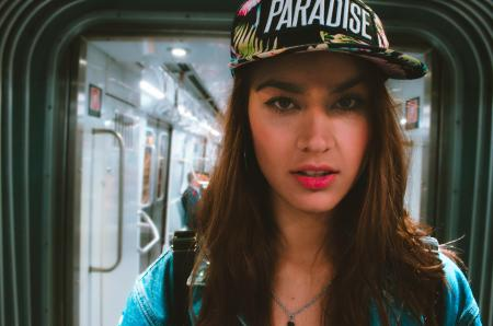 Woman in Blue Top Wearing Black and White Cap With Paradise Text-printed