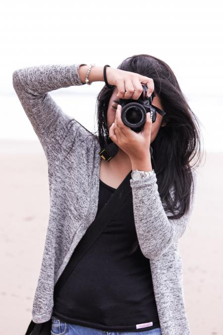 Woman in Gray Cardigan and Black Shirt Holding Black Dslr Camera