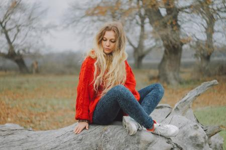 Woman in Red Sweater Sitting on Cutted Tree