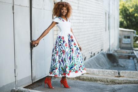 Woman in White and Multicolored Midi Dress Holding Door