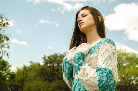 Woman in White and Teal Crochet Dress Under Cloudy Sky