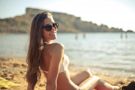 Woman in White Bikini Set Sitting Near Seashore