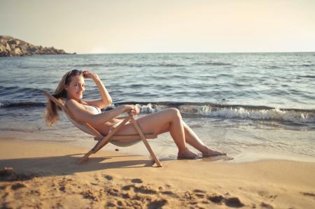 Woman Sitting on Sun Chair Beside Seashore at Daylight Photography