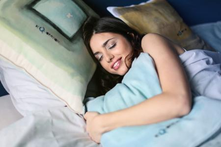 Woman Sleeping on White Bed Holding Blue Pillow