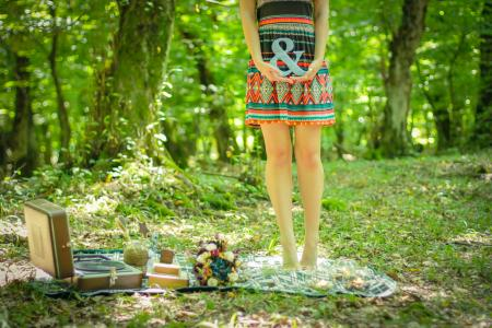 Woman Standing on Picnic Mat Holding Ampersand Lettering
