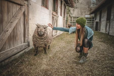 Woman Wearing Beanie Beside Sheep