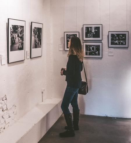 Woman Wearing Black Sweater and Blue Denim Jeans Staring at Paintings Inside Well-lit Room