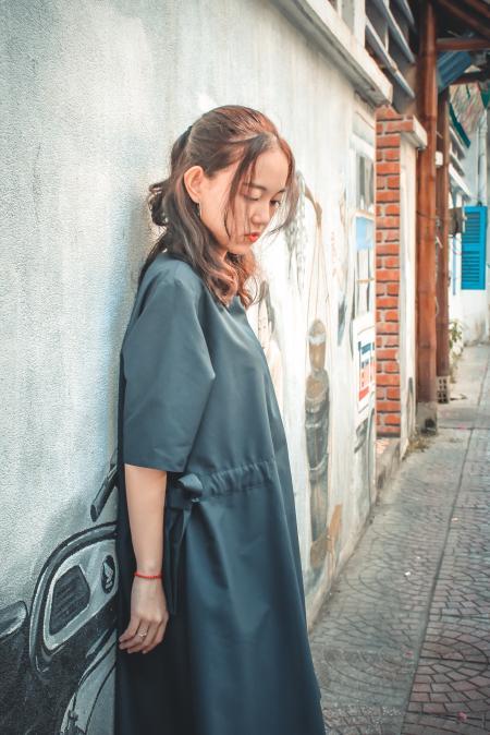 Woman Wearing Gray Coat Leaning on Gray Wall With Graffiti