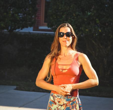 Woman Wearing Orange Strappy Neckline Tank Top and Blue, White, and Orange Floral Skirt