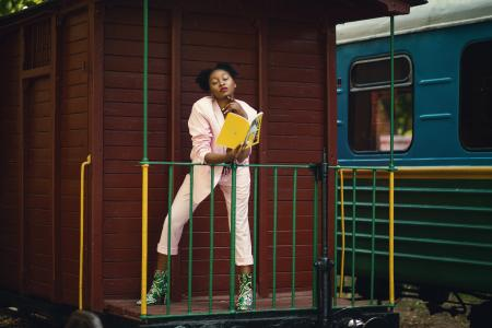 Woman Wearing Pink Blazer, Pants and Green Heeled Shoes Holding Yellow Covered Book