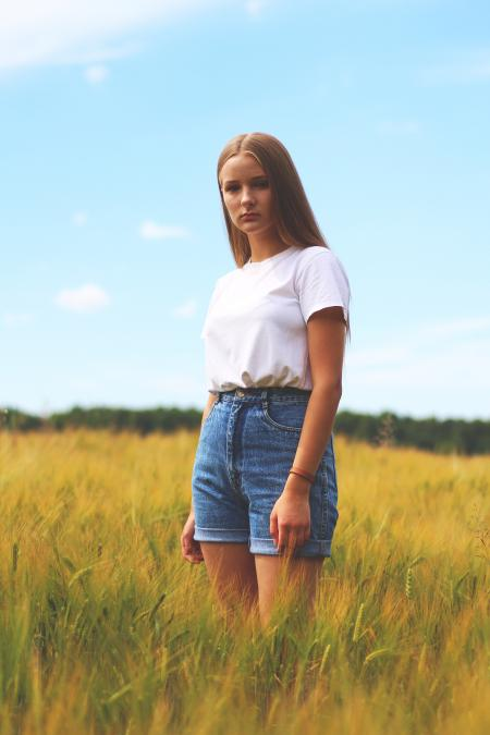 Woman Wearing White Crew-neck T-shirt, Blue Denim Cuff Short Shorts While Standing on Grass Field