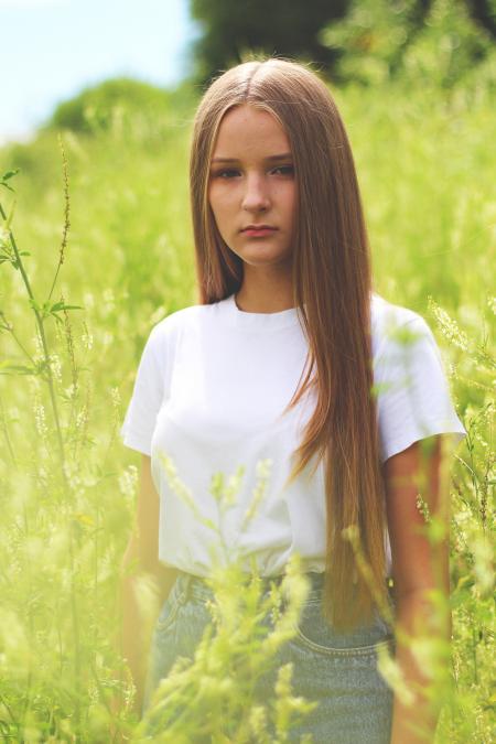 Woman Wearing White Shirt and Gray Denim Bottoms on Green Grass Field