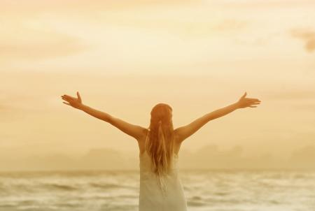 Woman with Raised Arms at Sunset on the Beach