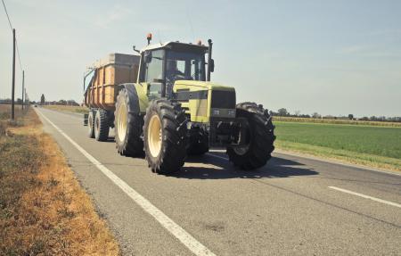 Yellow Tractor in Asphalt Road