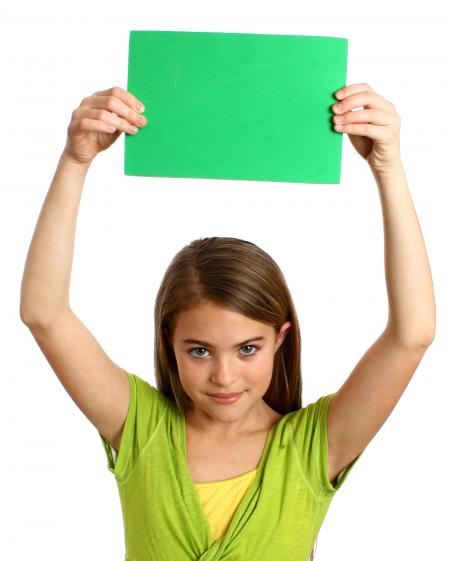 Young girl holding a blank green sign