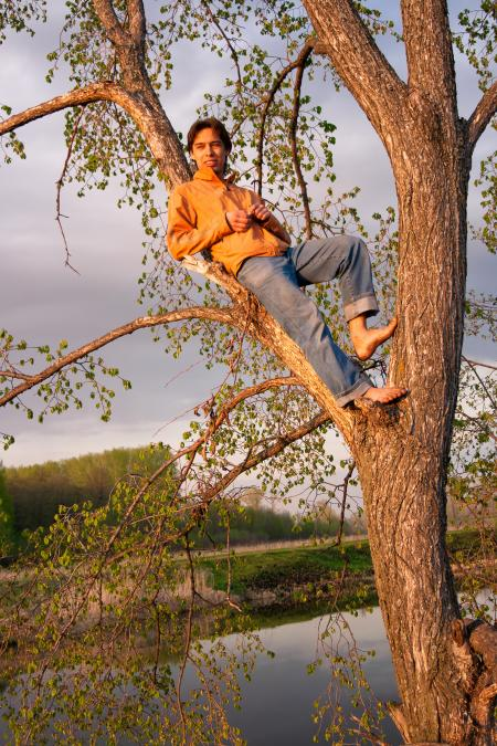 Young man relaxed on tree