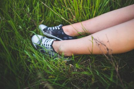 Youth sneakers on girl legs on grass