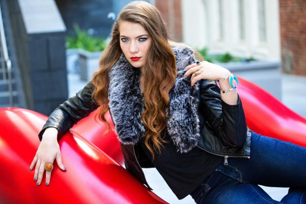 Closeup Photo of Woman Wearing Black Leather Fur-lined Jacket and Blue Denim Bottoms