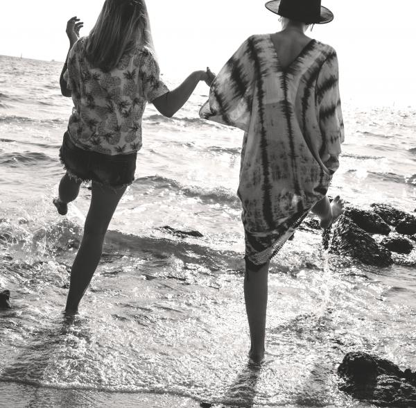 Grayscale Photograph of 2 Women Holding Hands While Walking on Sea Shore