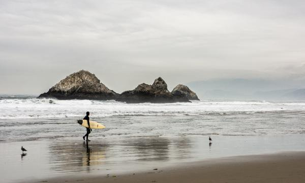 Man Carrying Surfboard in Front Bodies of Water on Brown Sand