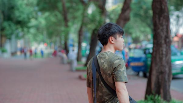 Man in Green and Grey Camouflage Shirt While Standing Behind Tree