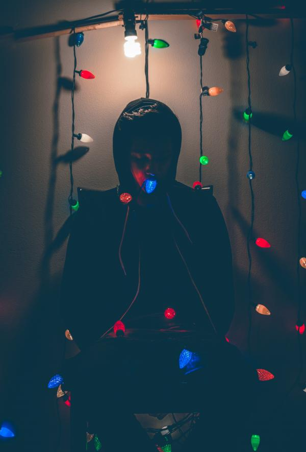Man Sitting on Chair With Multi-colored String Lights