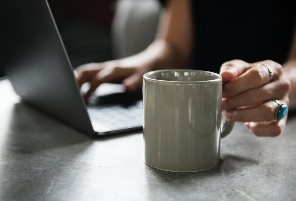 Person in Black Top Holding White Ceramic Mug and Using Laptop Computer